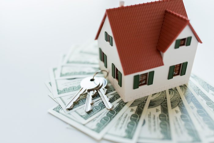 A miniature house on top of money with keys on the side