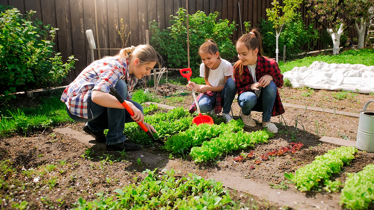 Happy young woman with daughters planting seeds in garden